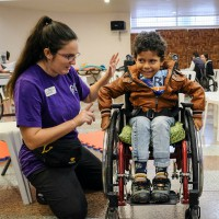 Alumna with boy in wheelchair